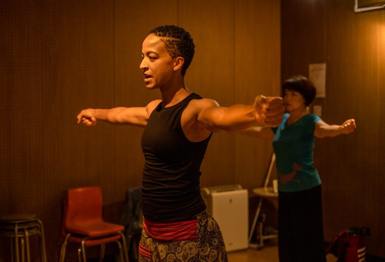 Black woman with black tank top. Her arms are straight out to the side, with hands in a fist in preparation for elbow isolations. Behind her is her student, a Japanese woman with a blue short sleeve shirt.